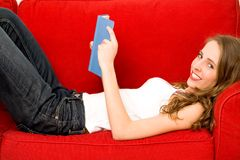 Woman reading book on couch Stock Photos
