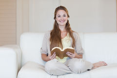 Woman reading a book on the couch Royalty Free Stock Photography