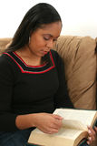 Woman Reading Book on Couch Royalty Free Stock Images