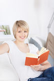 Woman reading a book on a couch Stock Images
