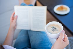 Woman reading book with cup of coffee Royalty Free Stock Images