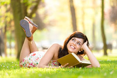 Woman reading book and day dreaming. Happy woman reading and holding story book in fresh green park on spring or summer. Caucasian brunette beautiful studentl stock photography