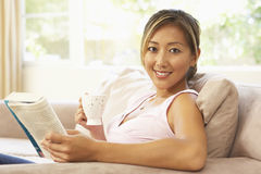 Woman Reading Book With Drink At Home Royalty Free Stock Image