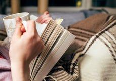 Woman reading book drinking hot tea Stock Photos