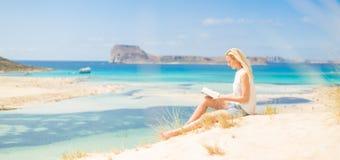 Woman reading book, enjoying sun on beach. Royalty Free Stock Image
