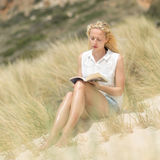 Woman reading book, enjoying sun on beach. Stock Image