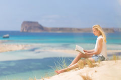 Woman reading book, enjoying sun on beach. Royalty Free Stock Image