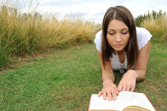 Woman reading book on field Royalty Free Stock Photography