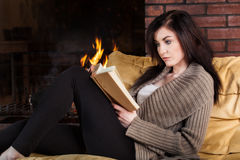 Woman reading a book by fireplace Royalty Free Stock Photos