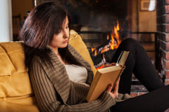 Woman reading a book by fireplace Royalty Free Stock Images