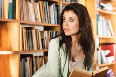 Woman reading a book in front of bookshelves stock images