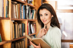 Woman reading a book in front of bookshelves Royalty Free Stock Photography