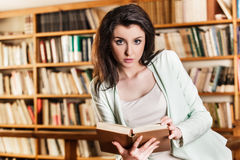 Woman reading a book in front of bookshelves Royalty Free Stock Images