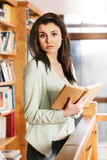 Woman reading a book in front of bookshelves Royalty Free Stock Photos