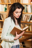 Woman reading a book in front of bookshelves royalty free stock photo