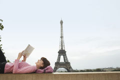 Woman Reading Book In Front Of Eiffel Tower. Side view of a young women lying on balcony and reading book in front of Eiffel Tower Royalty Free Stock Photography