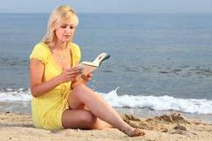 Woman reading book girl yellow dress. Woman reading a book girl the yellow dress water beach Stock Images