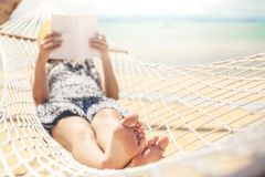 Woman reading a book on hammock beach in free time summer holiday stock images