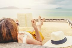 Woman reading a book on hammock beach in free time summer holiday