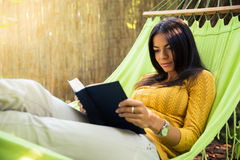 Woman reading book on hammok Royalty Free Stock Image