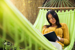 Woman reading book on hammok Stock Photos