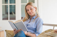 Woman reading book. Happy mature woman reading storybook on couch. Charming woman reading a novel sitting on a sofa in living room. Woman reading a book and royalty free stock image