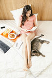 Woman reading the book and having breakfast. Stock Image