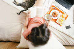Woman reading the book and having breakfast Stock Image