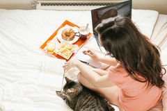 Woman reading the book and having breakfast Stock Photos