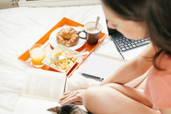 Woman reading the book and having breakfast Stock Images