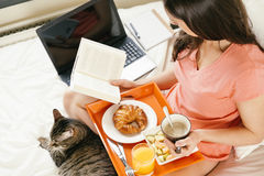 Woman reading the book and having breakfast. Stock Images