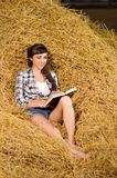 Woman reading book on haystack Royalty Free Stock Images