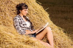 Woman reading book on haystack Royalty Free Stock Image