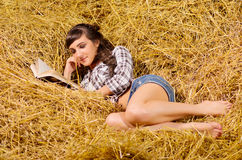 Woman reading book on haystack Royalty Free Stock Photos