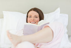 Woman reading a book on her bed Stock Images