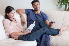 Woman reading a book while her fiance is watching TV Stock Photos