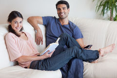 Woman reading a book while her husband is watching TV Stock Photography