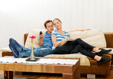 Woman reading a book while her husband is watching TV in living room Stock Image