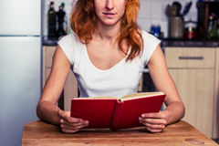 Woman reading a book in her kitchen Stock Photography