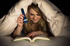 Woman reading book holding torch Royalty Free Stock Photos