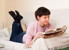 Woman reading a book. At home Stock Image
