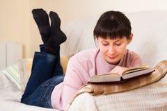 Woman reading a book. At home stock photos