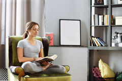 Woman reading book at home in the living room Stock Photo