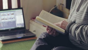Woman reading a book at home near laptop. stock footage