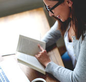 Woman reading a book in home office. Royalty Free Stock Images