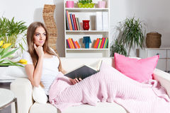 Woman reading book at home Stock Images