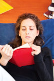 Woman reading book at home Stock Photography