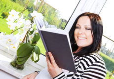 Woman reading book in house Stock Photos