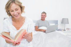 Woman reading book while husband is using laptop Stock Images