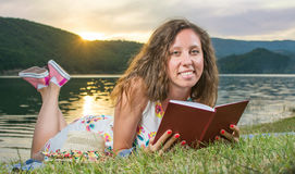 Woman reading a book by the lake. Solo relaxation Royalty Free Stock Image